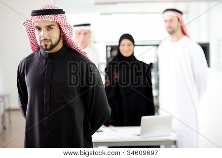 Confident arabic young business executive with his team in the background