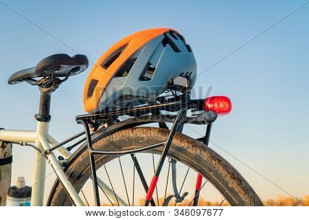 biking helmet on racks of a muddy touring bike with a red tail light against blue sky - safe riding, recreation and commuting concept