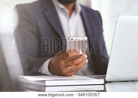 Close up of black businessman hand holding smartphone while working on laptop in modern office. Closeup of african hand using cellphone at desk. Mature man typing on mobile phone while working.