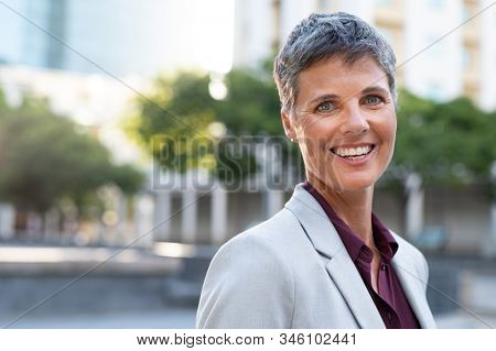 Portrait of senior businesswoman standing outdoor and looking at camera. Successful mature stylish woman in formal standing on city street. Confident entrepreneur smiling at sunset with copy space.