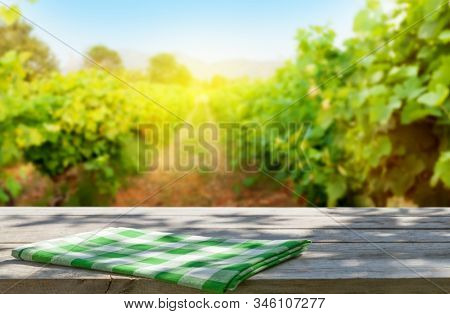 Wooden table with copy space in front of landscape of vineyard with copy space on wooden table. French countryside valley