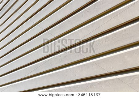 Part Of The Wall Of A Private House Covered With Plastic Beige Siding.