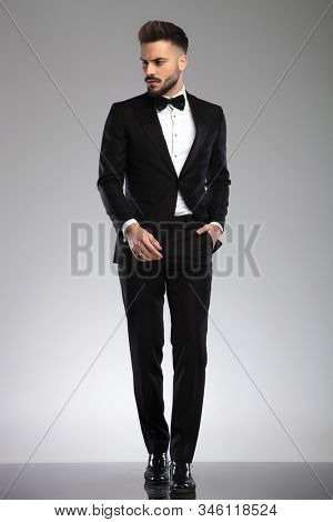 Bothered groom looking away and frowning, holding his hand in his pocket while wearing tuxedo, walking on gray studio background