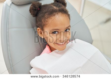 Charming Little Afro American Girl Sitting In Dental Chair Smiling And Looking At Camera. Little Fem