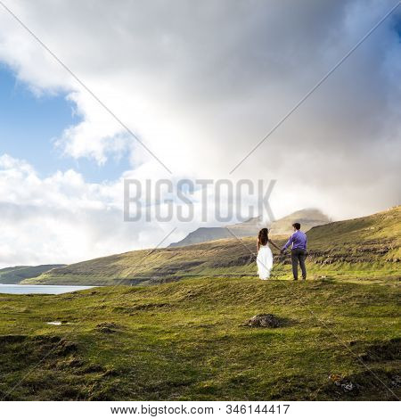 A Happy Couple In Wedding Dresses Or The Bride And Groom Holding Hands And Looking At The Picturesqu