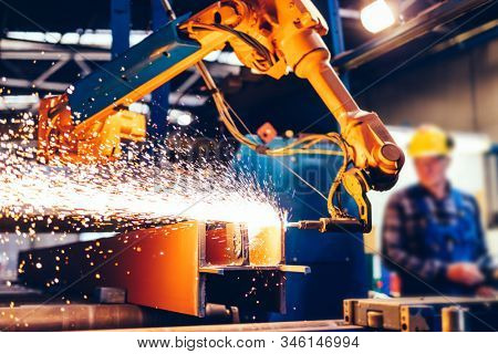 Worker controls robotic arm to cut steel in a factory. Modern heavy industry, technology and machine learning