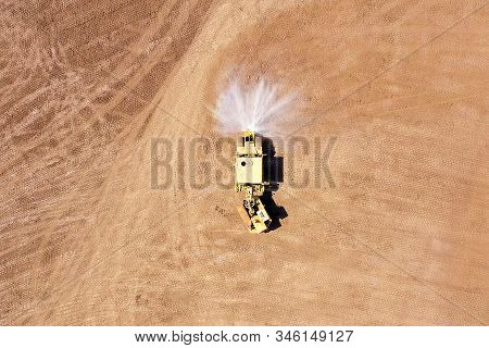 Articulated Water Truck Spraying Water On A Large Excavation Site  Ground For Dust Suppression And C