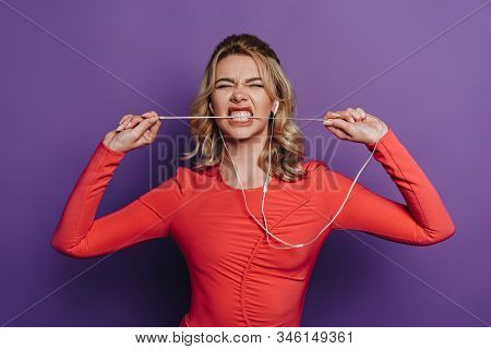 Thrilled Girl Biting Wire Of Earphones While Listening Music On Purple Background