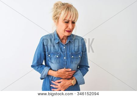 Middle age woman wearing casual denim shirt standing over isolated white background with hand on stomach because nausea, painful disease feeling unwell. Ache concept.