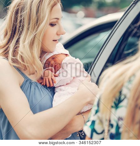 Young Mom With Her Newborn Baby Standing Near The Car.