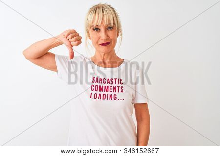 Middle age woman wearing fanny t-shirt with irony comments over isolated white background with angry face, negative sign showing dislike with thumbs down, rejection concept