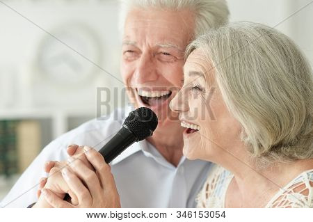 Close Up Portrait Of Senior Couple Singing Karaoke