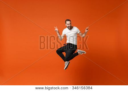 Funny Young Man In Casual White T-shirt Posing Isolated On Orange Background Studio Portrait. People
