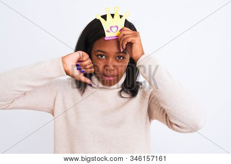 Young african american woman wearing pretend queen crown over isolated background with angry face, negative sign showing dislike with thumbs down, rejection concept