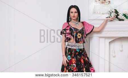 Portrait Of An Attractive Young Gypsy Woman Standing Near A Decorative Fireplace
