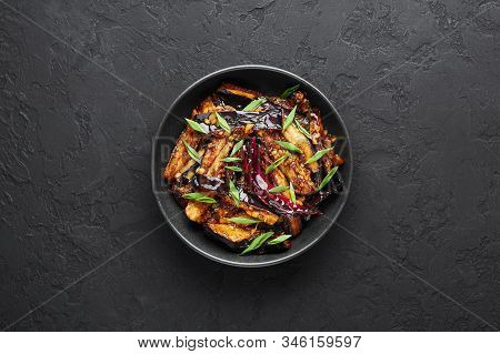 Sichuan Eggplant Stir Fry In Black Bowl At Dark Slate Background. Eggplant Stir Fry Is Chinese Cuisi