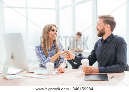 Young Employees With Coffee Glasses Sitting At The Desk