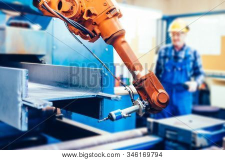 Worker operating robotic arm to cut steel in a factory. Modern heavy industry, technology and machine learning