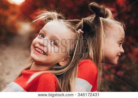 Twin Blondes Walk And Have Fun In The Autumn Forest Among The Red Trees.