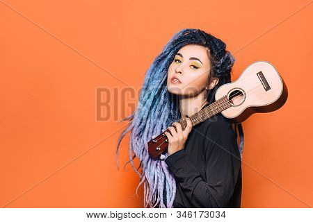Portrait Of Hipster Woman With Violet Dreadlocks And Ukulele In Her Hands On An Orange Background
