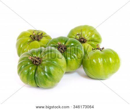 Heap Of Unripe Organic Heirloom Beefsteak Tomatoes Isolated On White