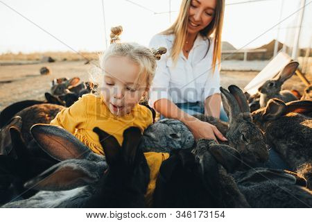 Mom And Daughter Visit A Petting Zoo With Rabbits On The Eve Of Easter. Holiday, Easter Traditions.