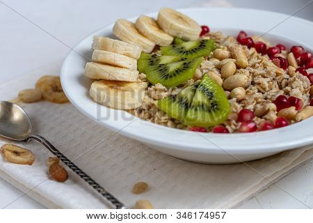 Breakfast Consisting Of Oatmeal, Nuts And Fruits. Kiwi, Banana, Pomegranate And Almonds Decorate The