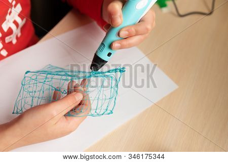 Close-up Hands Of Boy Creating Volume Plastic Figure With 3d Pen. Selective Focus. Education Concept