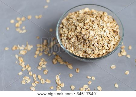Raw Oatmeal In A Transparent Bowl, Prepared For Brewing Porridge. Healthy Food, On A Gray Background