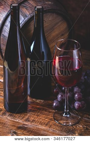 Glass Of Red Wine And Bottles With Grapes On A Wooden Surface With Wooden Barrel In Background