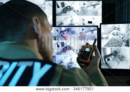 Security Guard With Portable Transmitter Monitoring Modern Cctv Cameras Indoors