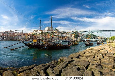 Portugal, City Landscape Porto, A Group Of Yellow Wooden Boats With Wine Port Barrels On Douro River