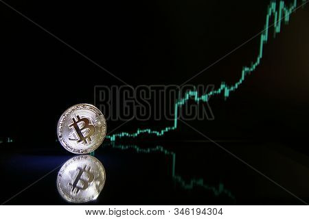 Bitcoin On The Background Of Bullish Stock Chart On A Black Background. Cryptocurrency Coin On Black