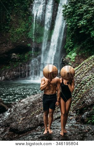 A Man And A Woman In Conical Hats At A Waterfall. The Couple Travels The World. Vacation In Asia. A