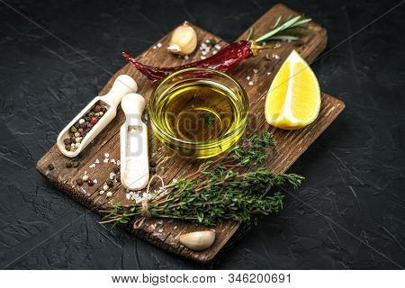 Selected Ingredients For Cooking. Lemon, Herbs, Olive Oil And Spices On A Cutting Board On A Dark St