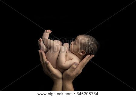 Newborn Naked Baby In Hands On A Black Background. Newborn Baby Hugs Daddy's Strong Arms. The Relati