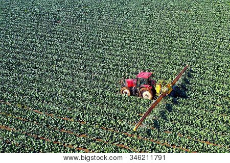 Pesticide Sprayer Tractor Working On A Large Field, Aerial Follow Footage.