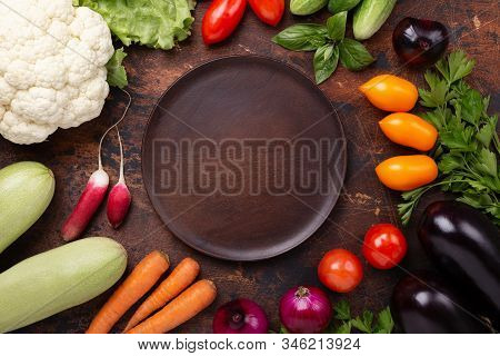 Brawn Wood Plate And Fresh Farmers Garden Vegetables On Wooden Table. Harvest Time. Top View - Image