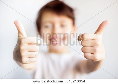 Closeup Of Dental Floss In Child Hands. Happy Child In White T-shirt Out Of Focus Hold Floss For Tee