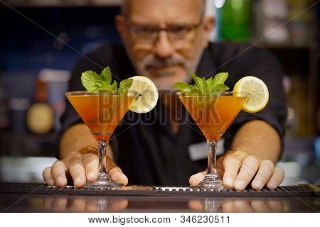 Elderly Bartender Gives Two Red Cocktail. Fresh Cocktail With Grapefruit. Alcoholic, Non-alcoholic D