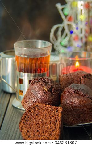 Chocolate Muffins On Black Wooden Background With Tea Glass In Iron Cup Holder. Homemade Chocolate C