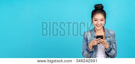 Banner Of Happy Asian Woman Feeling Happiness And Standing Typing Smartphone On Blue Background. Cut