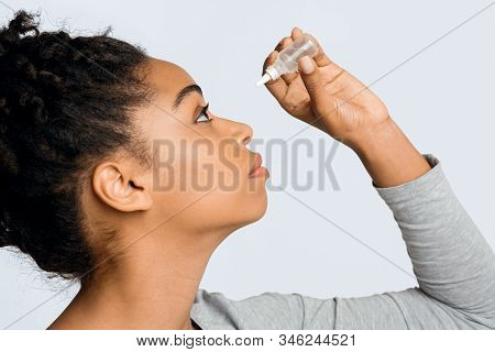 Black Young Woman Applying Ophthalmology Eyedropper, Side View. Glaucoma Eye Prevention, Human Visio