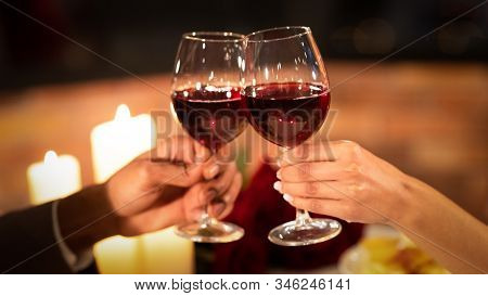 Cheers To Love. Unrecognizable Couple Clinking Red Wine Glasses Having Romantic Date In Fancy Restau
