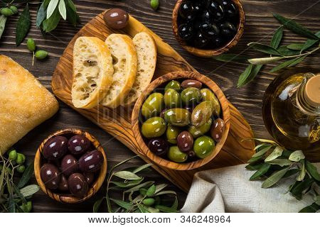 Olives, Olive Oil And Ciabatta Bread On Dark Wooden Table. Top View Copy Space.