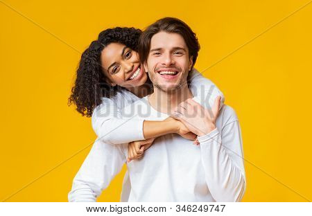 Portrait Of Young Interracial Couple In Love Cuddling And Posing Over Yellow Background, Smiling And