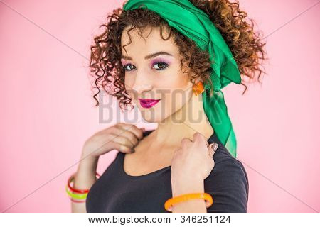 A Young Woman Of 30-35 Years Old With Curly Dark Hair Looks At The Camera, On Her Face Emotions Of H