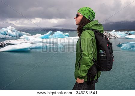 A Young Woman Tourist 30-35 Years Old Admires The Frozen Sea On The Coast Of Iceland, A Wild Cold Be