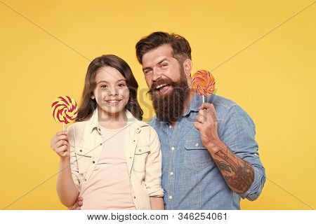 Sweets And Treats Concept. Daughter And Father Eat Sweet Candies. Sweet Childhood. Girl Child And Da