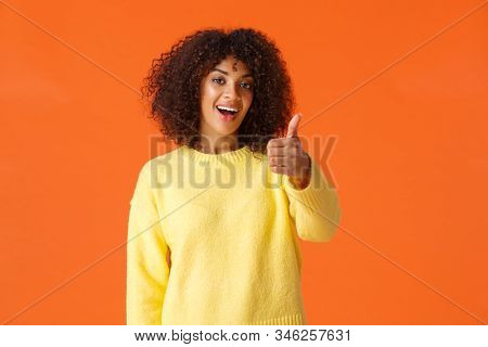 Cheerful Outgoing Modern African American Woman With Curly Hair, Showing Thumb-up In Like, Approval